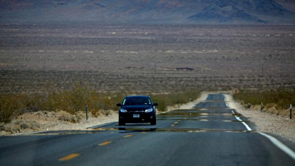 A car shimmers in the heat pouring off the asphalt on the highway leading in to Death Valley National Park on Sunday. People in the Southwestern U.S. are enduring Monday a fourth straight day of potentially record breaking heat.