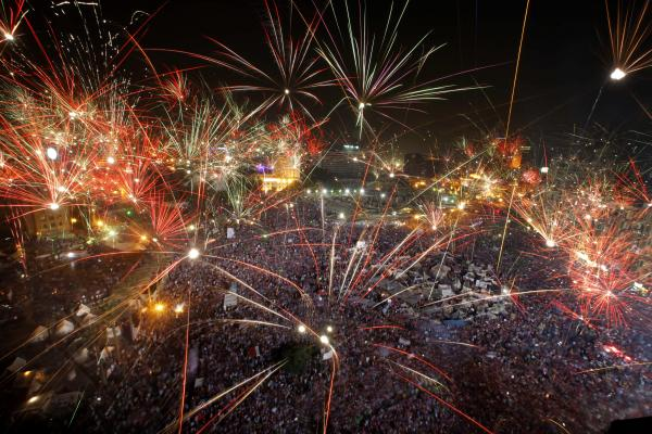 Fireworks light the sky Wednesday night as Morsi's opponents celebrate in Tahrir Square in Cairo.