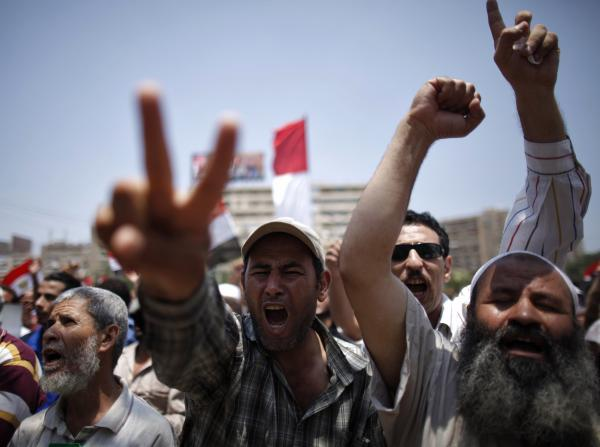 Supporters of Morsi shout slogans at the Raba El-Adwyia mosque square in Cairo. Arrest warrants have been issued for at least 300 Muslim Brotherhood leaders.