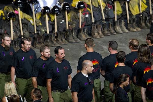 Former Granite Mountain Hotshot firefighters walk past ceremonial firefighter boots and gear during a memorial honoring 19 fallen firefighters in Prescott Valley, Ariz., on Tuesday.