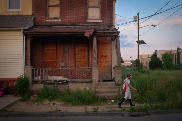 "Angel Ramirez, a North Camden Little League player, walks through the Sixth Street drug corridor, known as ""Heroin Highway,"" on his way home from practice in Camden, N.J. The Little League program is aimed at keeping kids in the struggling city engaged in a sport after school."