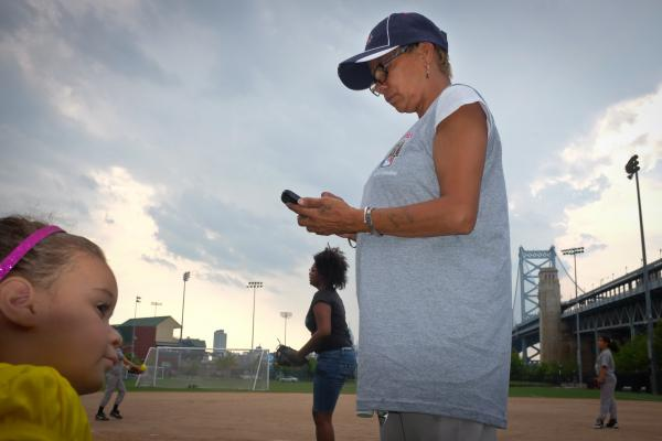Maria Reyes, a coach for the girls Little League teams, calls players to make sure they are coming to practice at the Rutgers field.