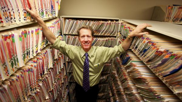 Dr. James Kinsman stands in the practice's records room, surrounded by patient files that date back only two years.
