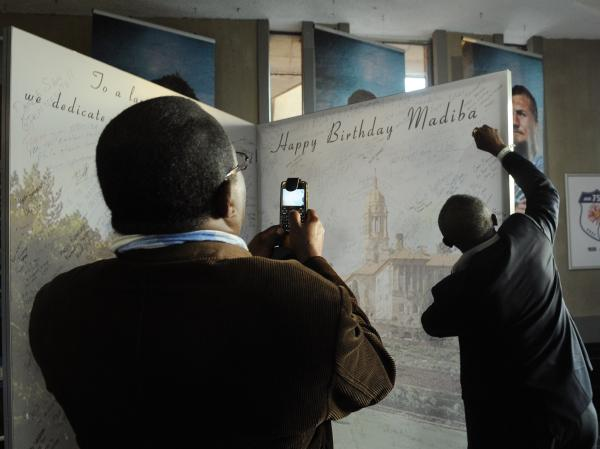 A man signs a large birthday card at Loftus Stadium in Pretoria for ailing former South African President Nelson Mandela's upcoming July 18 birthday. 'Madiba' is Mandela's clan name.