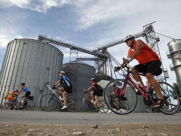 Cyclists pass a grain elevator in <em>The Des Moines Register</em>'s annual bike ride across Iowa in 2011. NPR correspondents are joining the ride this year and documenting the journey.