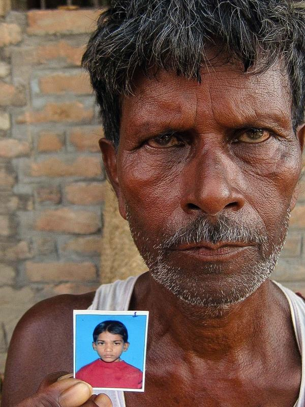 Makeshwar Ram holds up a picture of his grandson, whom he buried in front of the elementary school where the boy ate his last meal.