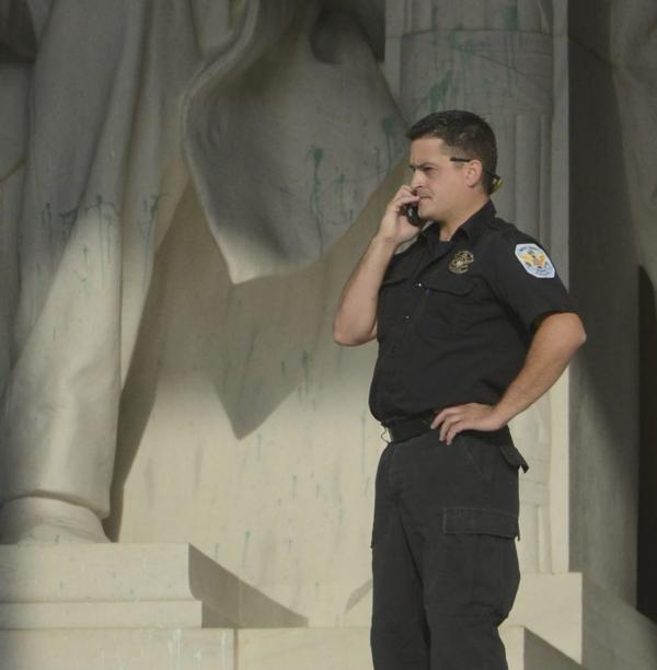 A police officer stands near the statue of the 16th president at the Lincoln Memorial, which was splattered with paint Friday morning.