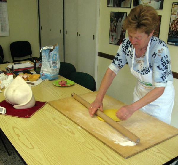 Grazia Battistini, 63, has been been making tortellini as a <em>sfoglina </em>for about 50 years. A statue of the ideal tortellino shape sits in the foreground.
