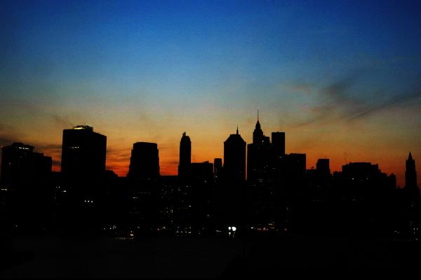 The sun sets over the Manhattan skyline during a major power outage affecting a large part of the Northeastern United States and Canada on Aug. 14, 2003. Ten years later, some improvements have been made to the grid to prevent another large-scale blackout.