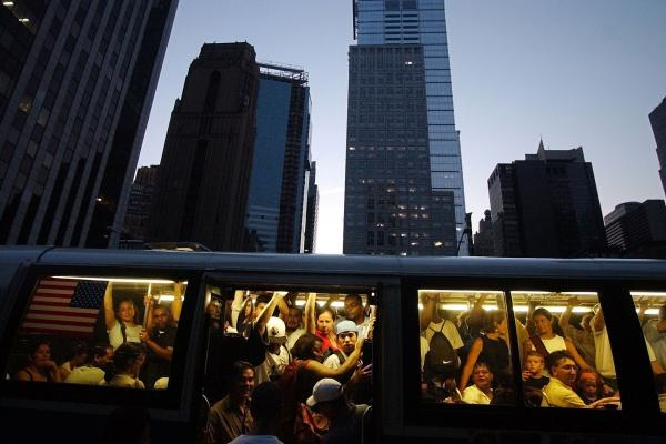 People try to board the back of a crowded New York City bus during the blackout.