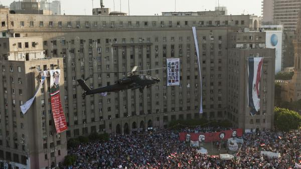 An Egyptian Apache helicopter flies over a crowd of pro-military demonstrators at Tahrir Square in Cairo on July 26. U.S. firms supply military hardware to the military, including the Apache helicopters.