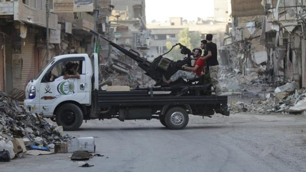 Free Syrian Army fighters man an anti-aircraft gun on the back of a truck in Deir al-Zor on Tuesday.