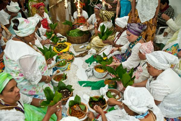 People serve sacred food at the Olubaje party. The food is wrapped in leaves from the castor oil plant.
