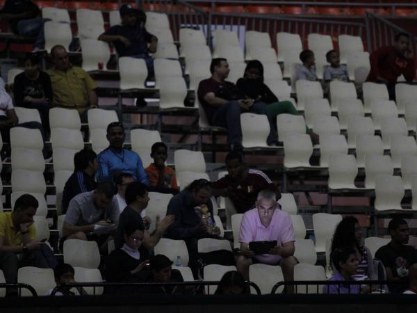 Fans wait for play to resume Tuesday at a FIBA World Cup qualifying basketball game in Caracas, Venezuela. A blackout left about 70 percent of the country without electricity.