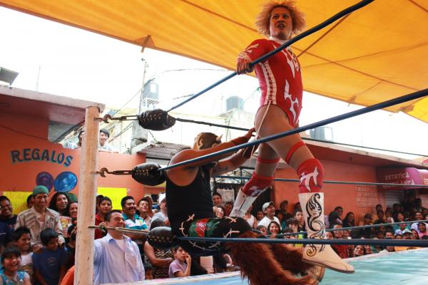 Pasión Kristal performs a signature move on an opponent in Magdalena Culhuacán, on the outskirts of Mexico City. Gabriel Centella Damian wrestles as an<em> Exótico — </em>campy male, mostly gay, professional wrestlers — under the stage name Pasión Kristal. Despite their makeup and feminine clothes, <em>Exóticos</em> are some of the best wrestlers.