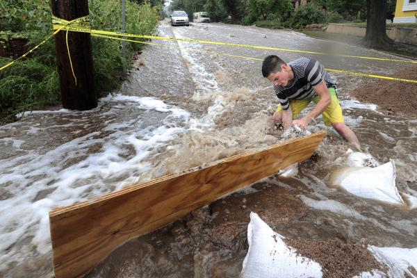 Jake Bennett uses sandbags and plywood to help funnel water down a street in Boulder.