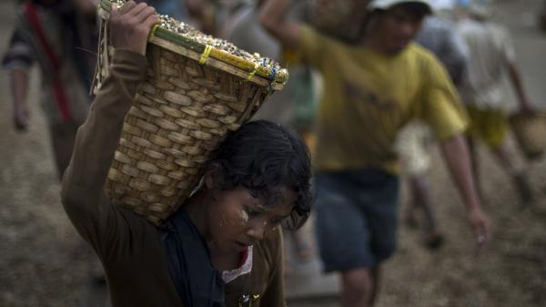 A child carries a basket of stones while unloading a quarry boat with adult workers at a port in Yangon, Myanmar, last year. The U.N. says more than a third of the country's children have jobs.