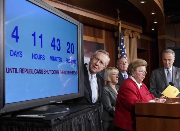 Senate Majority Leader Harry Reid, D-Nev., looks at a countdown-to-shutdown clock during a news conference in the Capitol on Thursday.