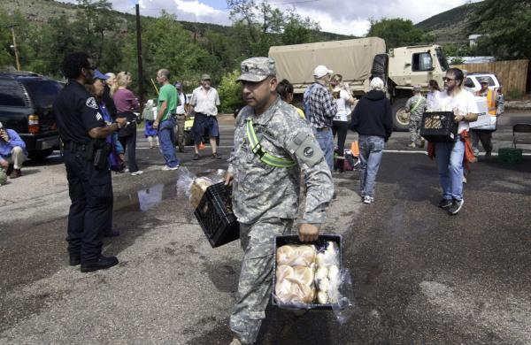 A National Guard soldier carries bread into Lyons, Colo., Sept. 13, 2013. Access to the small mountain town was cut off after bridges were destroyed by flash flooding. (Kenneth Wajda/AP)