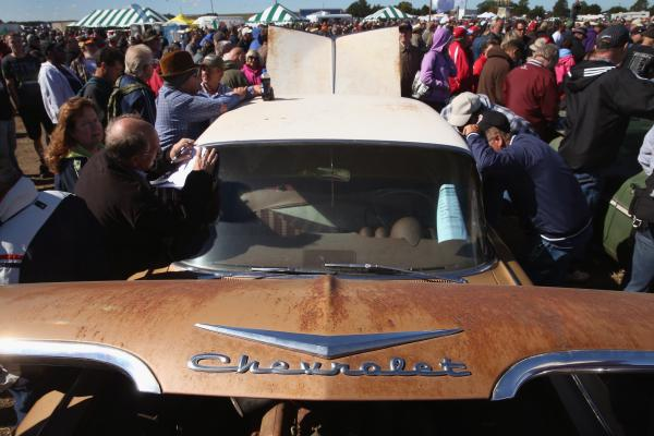 Buyers and spectators gather around a 1959 Impala as an auctioneer calls out bids for classic cars and trucks being sold at the Lambrecht family farm Saturday, Sept. 28, in Pierce, Nebraska.