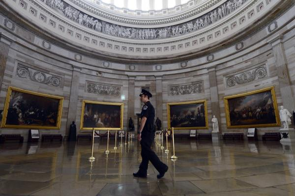 A Capitol police officer walks through the Capitol Rotunda, empty of visitors after being closed to tours Tuesday because of the government shutdown.