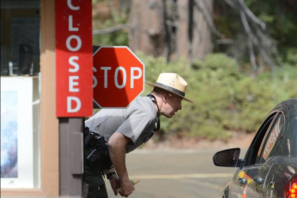 Park ranger Jeff Gardner tells visitors to Yosemite National Park that the park is closed. Day visitors were allowed to pass through Yosemite but were instructed not to stop or use any facilities.