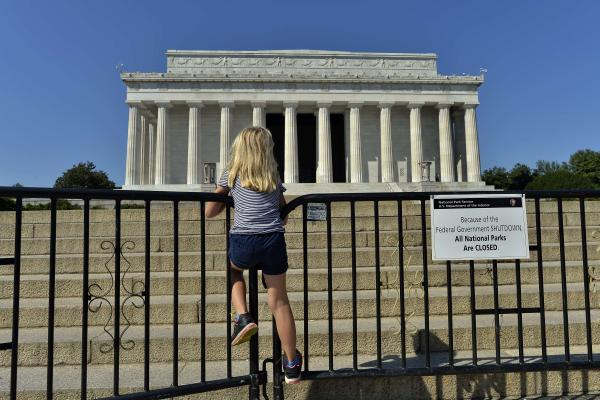 A child stands on the barricade around the Lincoln Memorial. President Obama called congressional leaders to a White House meeting on Wednesday, providing a glimmer of hope that the shutdown may end soon.