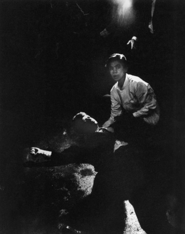 Rigid, semiconscious, his face an ashen mask, Sen. Robert Kennedy lies in a pool of his own blood on the concrete floor, a bullet deep in his brain and another in his neck. Juan Romero, a busboy whose hand Kennedy had shaken before the shots, tried to comfort him.