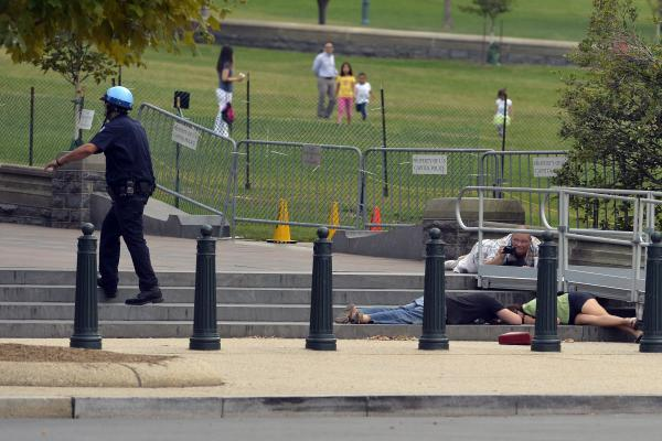 People take cover after gunshots were heard near the Capitol.