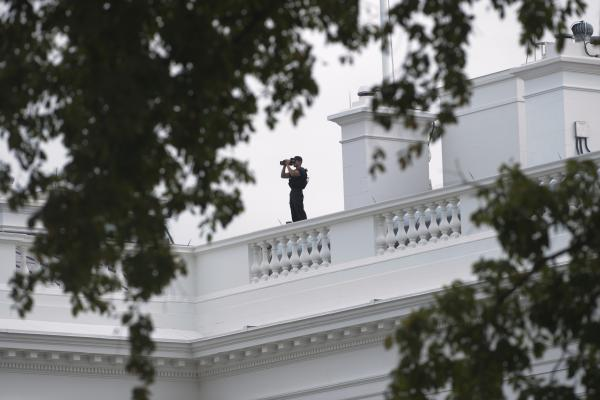 A member of the Secret Service looks out from the roof of the White House.