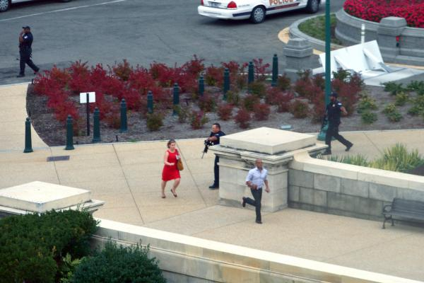 People run for cover as police converge to the site of a shooting on Thursday on Capitol Hill in Washington, D.C. The U.S. Capitol was placed on security lockdown after shots were fired outside the complex, senators said.