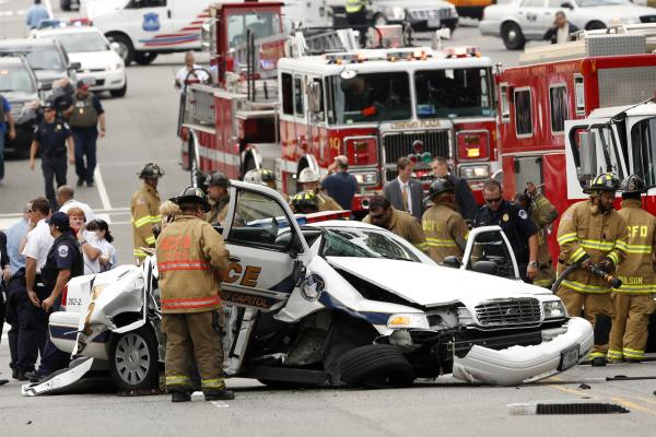 Rescue personnel surround a smashed Capitol Police car.