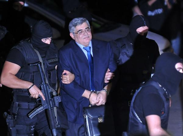 Michaloliakos is escorted by masked police to an Athens court.