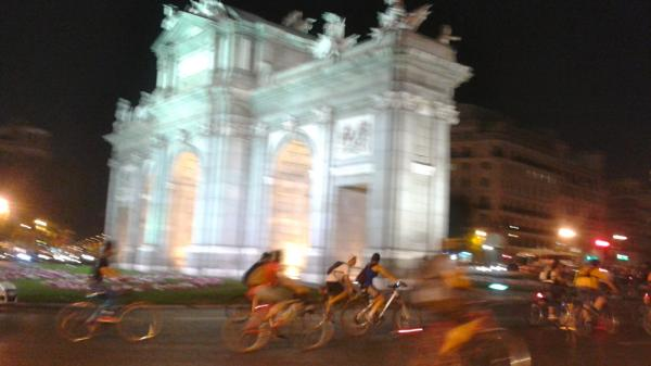 Cyclists whiz past Madrid's Puerta de Alcalá monument as part of <em>Bici Crítica,</em><em> </em>a movement that seeks to raise awareness of bike safety. On the last Thursday of every month, thousands of cyclists ride in unison through downtown Madrid, blocking traffic during rush hour.
