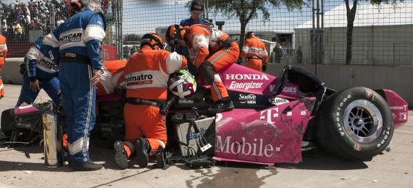 A safety team works to remove Dario Franchitti from his car after a high-speed crash at the IndyCar Grand Prix of Houston Sunday. The driver was hospitalized with a fractured spine and other injuries.