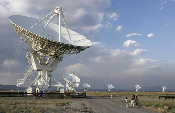 "Tourists are dwarfed by the <a href=""http://www.vla.nrao.edu/"">Very Large Array</a> in 2005. The facility, on the Plains of San Agustin, 50 miles west of Socorro, N.M., has been closed as a result of the government shutdown. The VLA consists of 27 radio antennas linked together to simulate the capabilities of a single dish 17 miles in diameter."