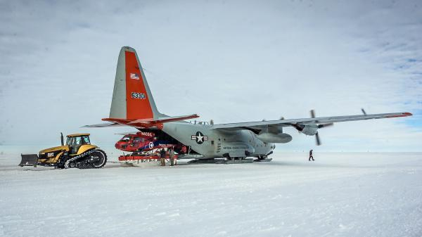 A helicopter is unloaded from an LC-130 in Antarctica last December. Researchers on this mission were studying the Pine Island Glacier, one of the fastest-receding glaciers on the continent.