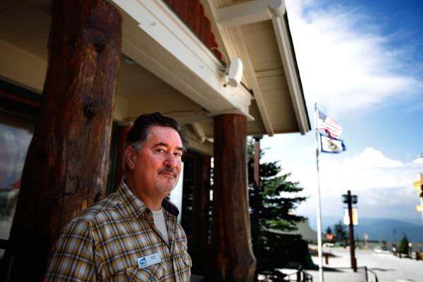George Murphy is the IT director of Snowshoe Mountain Resort, which is within the 10-mile radio quiet boundary of the NRAO telescope. He's had to find inventive ways to bring connectivity to the resort, including installing short-range cell receivers like the one shown here, mounted on the building behind him.
