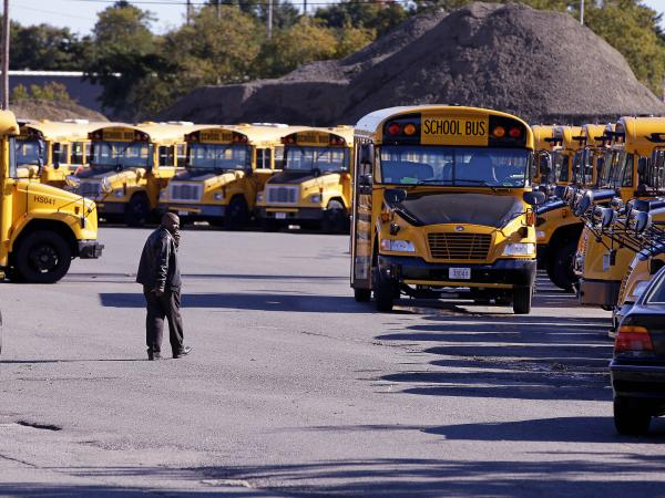 School buses sit idle in a lot at Veolia Transportation, Boston's school bus contractor, on Tuesday