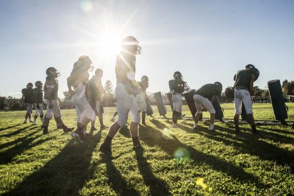 Football practice at Castro Valley High School in California. Proper hitting technique requires players to keep their heads up to prevent neck injuries and concussions.
