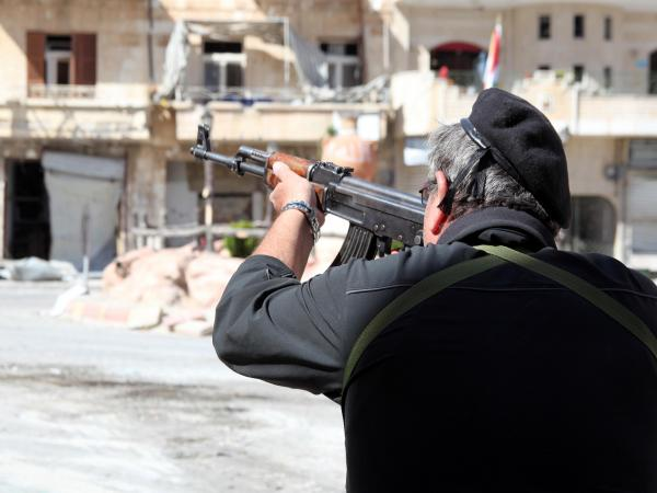 A Syrian soldier takes aim at rebel fighters positioned in the mountains of the town of Maalula in September.