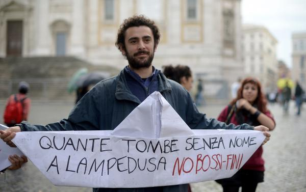 "An Italian student holds a paper boat reading ""How many tombs without names in Lampedusa, No to Bossi Fini"" in reference to the recent tragedy near Lampedusa island where at least hundreds of immigrants drowned and the Bossi-Fini anti-immigration law."
