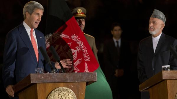 Secretary of State John Kerry describes a new partial bilateral security agreement with Afghanistan, in a news conference held Saturday after hours of discussions with Afghan President Hamid Karzai, right.