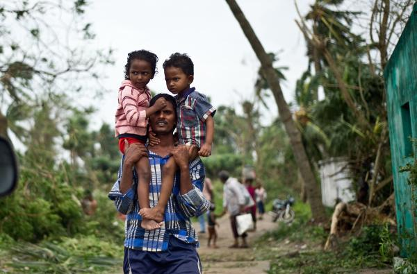 A displaced Indian man carries his children at Sonupur village, outside Gopalpur on Sunday.