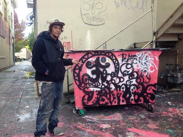 "22-year-old ""James"" from Tillamook, Oregon shows off his graffiti art in an Olympia alleyway."