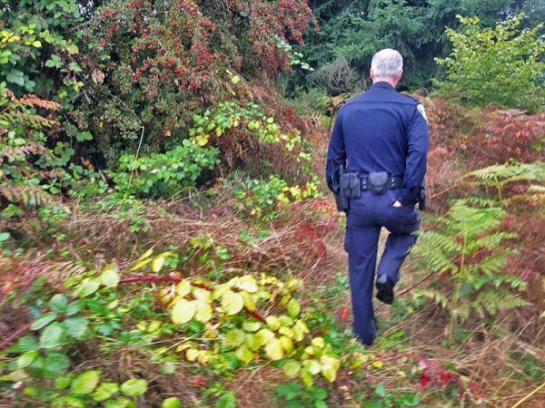 Lt. Paul Lower of the Olympia Police Dept. heads into a former homeless camp in Olympia where a murder took place last fall.