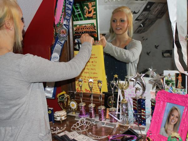 Daisy Coleman, now 16, looks at trophies and other awards she's won for beauty pageants, dancing and sports. She has attempted suicide at least twice since waking up in freezing temperatures on her doorstep.