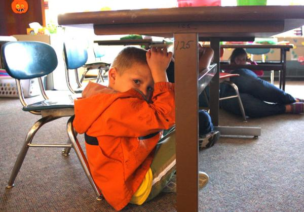 Kindergartener Jesse Clark practices getting under his desk during an earthquake drill at Finch Elementary in Spokane.