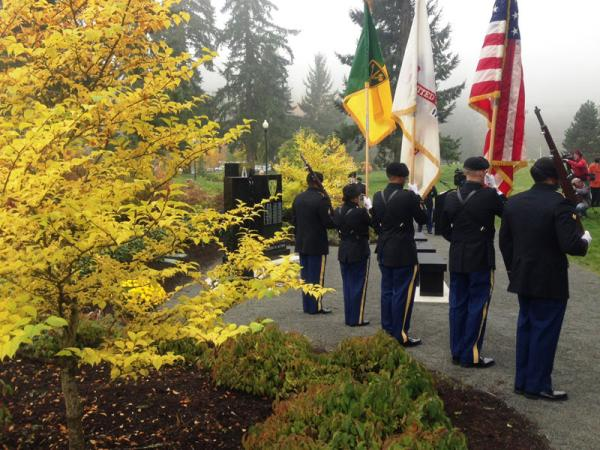 A color guard flanks a new memorial to 29 members of a Joint Base Lewis-McChord military police brigade killed in action between 2003 and 2011.