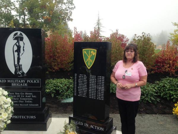 Debbie Ward stands next to a new Joint Base Lewis-McChord memorial that includes the name of her son, PFC Aaron Ward, who was killed in Iraq in 2008.